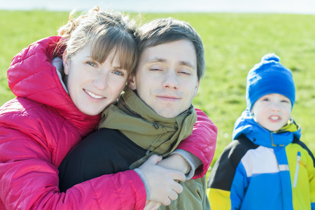 wooly: Family portrait of hugging parents with preschooler son at the background