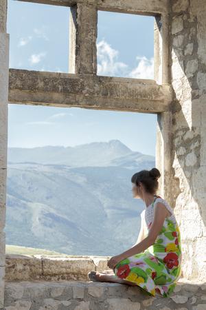 snění: Pohled zezadu na mladou ženu v sundress se dívá na pohled z okna