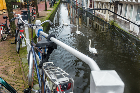 Canal with tunnel and historic street with bicycle parking lot in Dutch Delft old city
