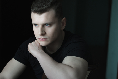 Young man with hand on shoulder low-key lighting indoor dark portrait
