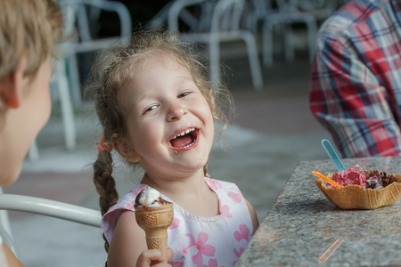 bond street: Little girl and her sibling brother are laughing during eating Italian ice cream
