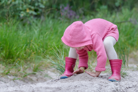 Preschooler girl is playing with sand in summer forest Stock Photo