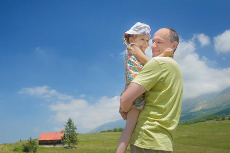 Padre emozionante che tiene piccola figlia sul suo prato verde alta persone anziane Archivio Fotografico - 86179180