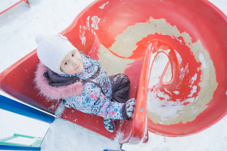 Winter activity of little girl on red spiral plastic playground slide