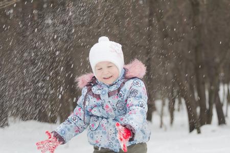 La bambina che ride sta lanciando neve invernale con le sue mani Archivio Fotografico - 88283984
