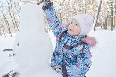 La bambina è decorare il pupazzo di neve invernale all'aperto Archivio Fotografico - 88283985