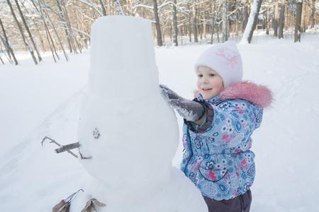 Bambina allegra sta facendo snowman di tre palloni dalla neve Archivio Fotografico - 88283986