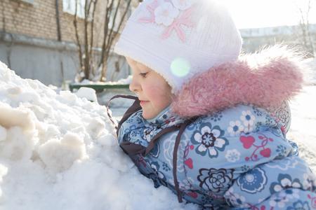 Profili il ritratto all'aperto dell'inverno di giocare la bambina in collina della neve Archivio Fotografico - 88283988