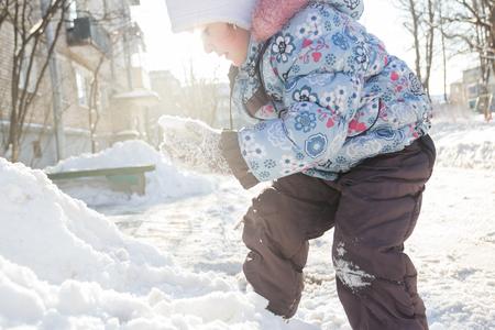 La bambina in abiti caldi invernali sta scalando la neve Archivio Fotografico - 88283989