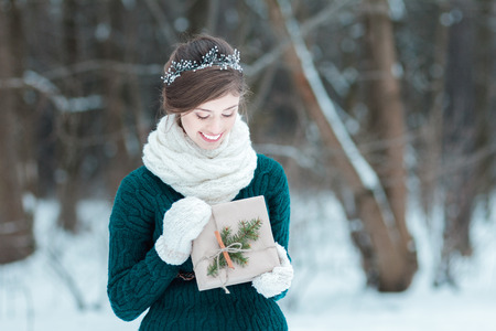 Smiling young woman holding Christmas gift in hands