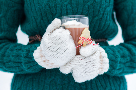 Guanti lanosi donna con cacao caldo natalizio con caramelle gommosa e molle in tazza di vetro trasparente Archivio Fotografico - 90765462