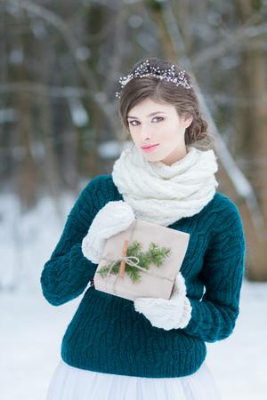 Regalo di Natale della tenuta della giovane donna graziosa in mani Archivio Fotografico - 91103623