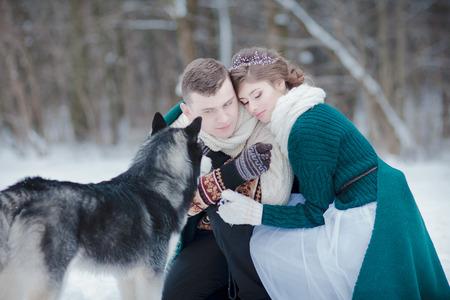 Ami le coppie con il husky siberiano nella foresta nevosa dell'inverno all'aperto Archivio Fotografico - 94124833