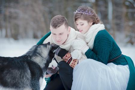 Amanti felici sulla foresta di inverno che camminano con il husky siberiano all'aperto Archivio Fotografico - 94192207