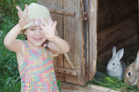 Laughing girl showing hands in front of farm hutch with domestic rabbits outdoors