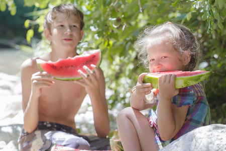 Beach picnic with juicy watermelon of two siblings in summer shade Archivio Fotografico
