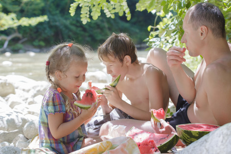 Family picnic of father and two children with juicy watermelon in hot summer day Archivio Fotografico