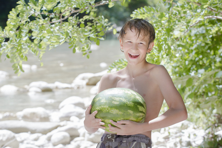 Teenager boy holding fresh green watermelon in his hands