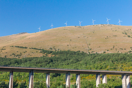 An elevated highway viaduct in Italian mountains, Abruzzo underneath the wind turbines