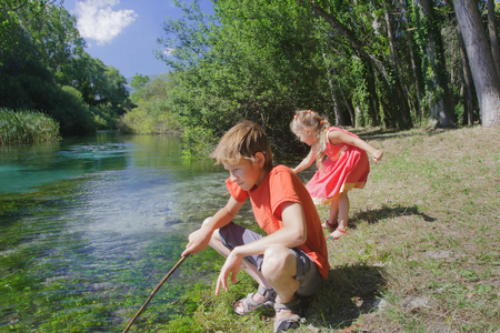 Siblings summer recreation activity outdoor game on Italian Tirino river bank in sunny day Archivio Fotografico