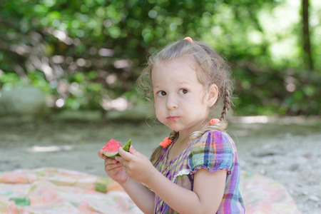 Blonde little girl biting juicy watermelon slice on summer beach picnic