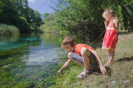 Two siblings playing on Italian Tirino river bank with little stick