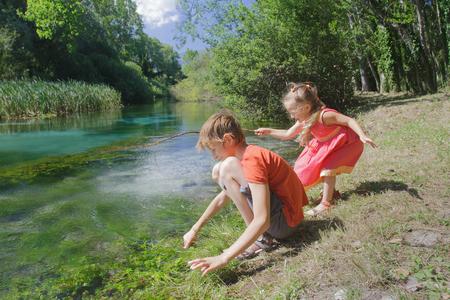 Fratelli germani del ragazzo e della ragazza che giocano vicino all'acqua del fiume italiano di Tirino in Abruzzo Archivio Fotografico - 95878255