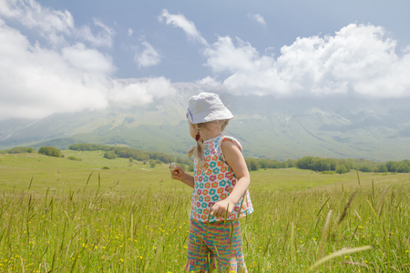Back view of blonde little girl in Italian Apennines of Abruzzi region looking at summer mountains