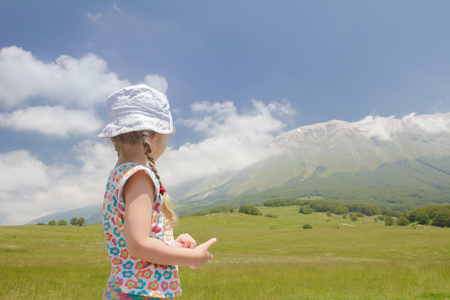Rare view of Caucasian girl in Italian Apennines of Abruzzi region looking at high mountains