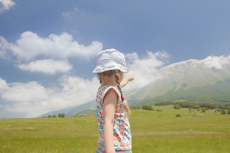 Little girl in Italian Apennines of Abruzzi region pointing at big mountain ridge view