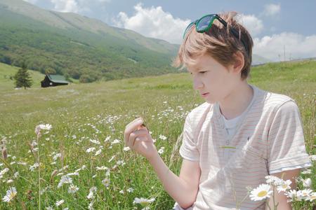 Teenager boy examining green grasshopper at alpine mountains summer landscape background