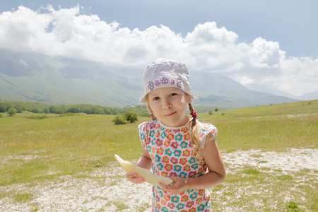 Little girl with melon slice in hand enjoying being on summer Alpine meadow