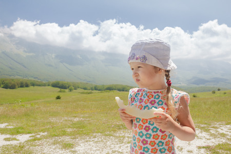 Eating sweet melon slice little girl enjoying great Alpine view Archivio Fotografico