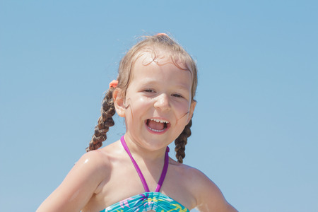 Close-up outdoors beach portrait of laughing happy little girl kid Archivio Fotografico