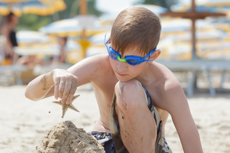 Concentrated beach boy is building sand castle with starfish on top