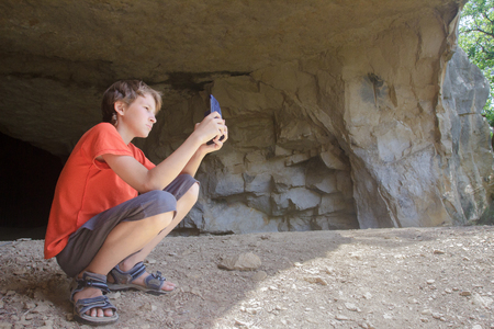 Traveler taking photo of rocky landscape with camera phone from natural mountain cave