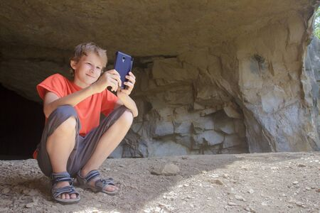 Boy hiker taking picture of mountain landscape with camera phone from natural rocky cave