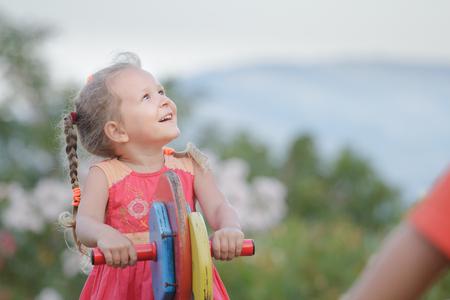Attività ricreativa della ragazza del bambino che oscilla sull'estate di legno dell'attrezzatura del campo da giuoco all'aperto Archivio Fotografico - 97521161