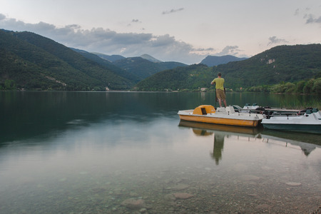 Man on pedalo or paddle boat is chilling out on Italian Scanno mountain lake