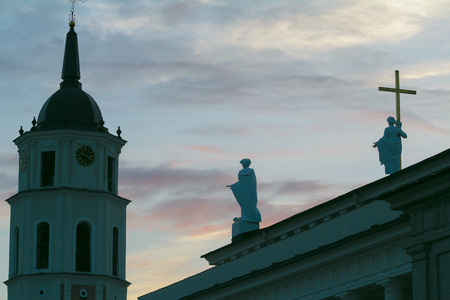 Sculpture silhouettes of Saint Helena and Saint Casimir on Cathedral Basilica of St. Stanislaus and St. Ladislaus roof and Cathedrals Belfry tower in Vilnius Lithuania at dusk