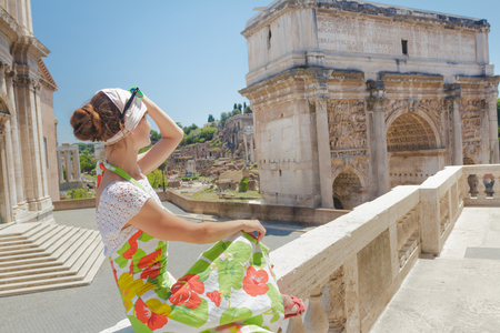 Beautiful woman in flower dress on tourist viewpoint looking at view of Palatine Hill