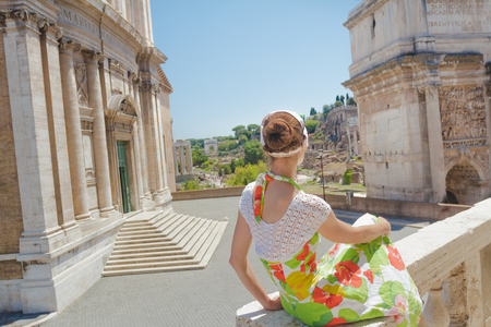 Pretty woman in floral dress on tourist viewpoint looking at view of Palatine Hill on Roman Forum ancient ruins with Arch of Septimius Severus and Santi Luca e Martina church outdoors Archivio Fotografico
