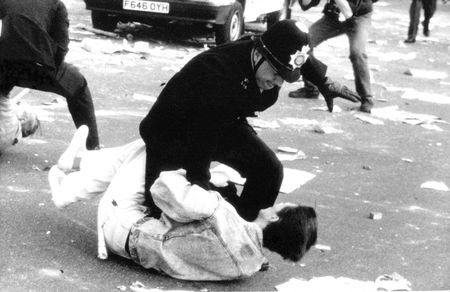protest: London, England - March 31, 1990 - A British police officer grapples with a protestor during the Poll Tax Riots in Trafalgar Square.