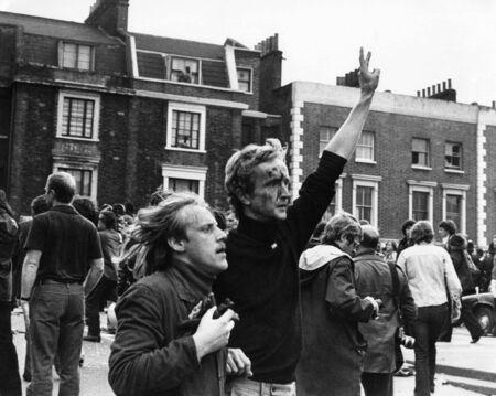 Londra, Inghilterra - intorno al 1976 - un uomo ferito � condotto via dopo scontri tra manifestanti e il partito nazionale anteriore a Brixton. Editoriali
