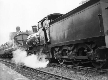 Sheffield Park, England - circa 1972 - A steam locomotive pulls a passenger train into Sheffield Park station on the preserved Bluebell Line Railway.