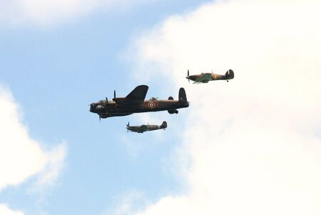 escorted: Eastbourne, England - August 16, 2009 - The Battle of Britain Memorial Flight consisting of a Lancaster bomber escorted by Hurricane and Spitfire fighters, flys past at an airshow.