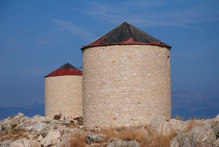 emborio: Two old stone windmills on the hills above Emborio on the Greek island of Halki.
