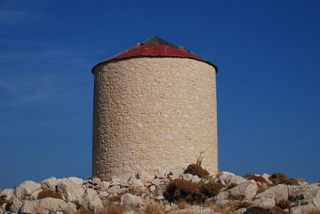 halki: An old stone windmill on the hills above Emborio on the Greek island of Halki.