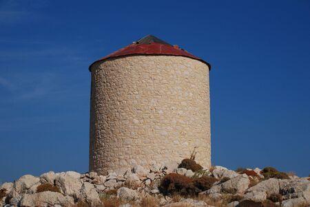emborio: An old stone windmill on the hills above Emborio on the Greek island of Halki.