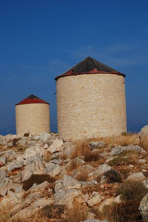 halki: Two old stone windmills on the hills above Emborio on the Greek island of Halki.